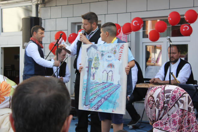 Kirsten Kötter: Ender Cetin shows my painting during a special event. A boy holds my painting (photography 2014-06-22)